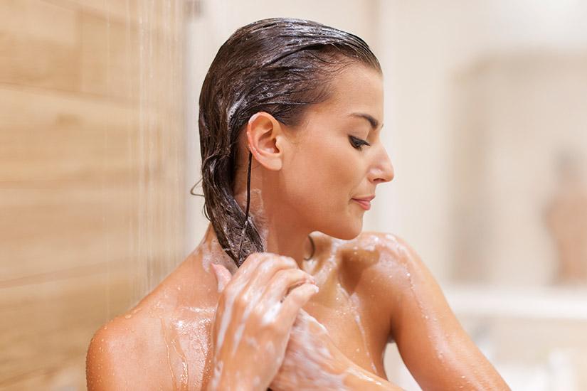 Widok kobiety myjącej włosy