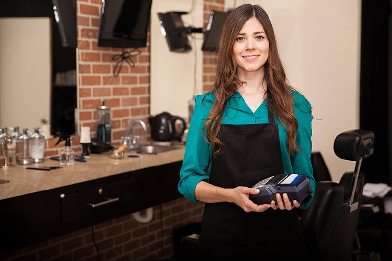 fryzjerka z kasą fiskalną online w dłoniach
