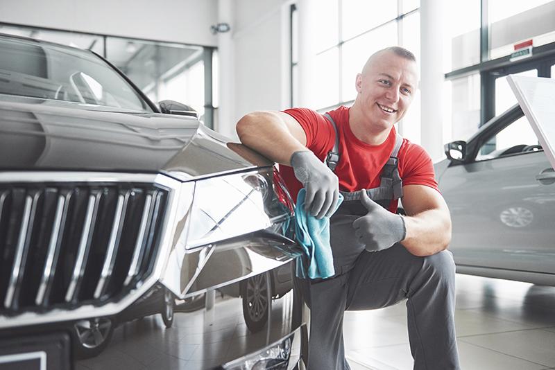 Profesjonalista poleruje karoserię w myjni samochodowej.
