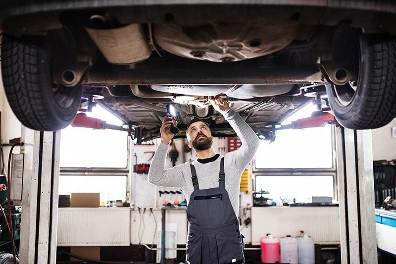 Mechanik naprawia auto w garażu.
