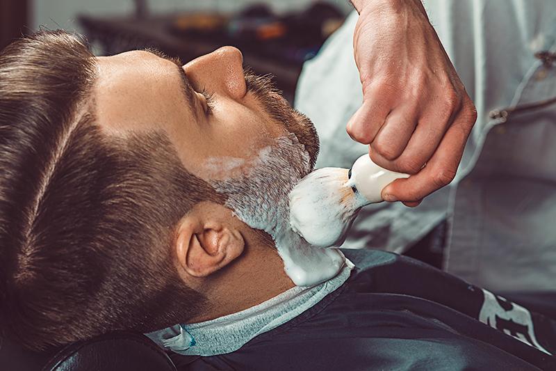 Barber nakłada pędzlem piankę do golenia na zarost na policzkach.