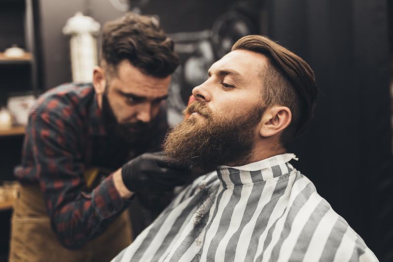 Barber przycinający długą brodę młodemu mężczyźnie.