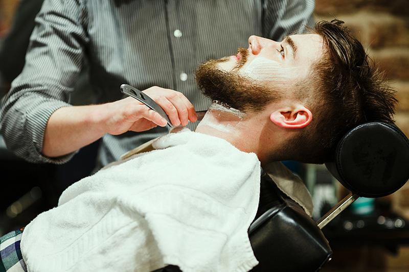 Barber goli brodę brzytwą.