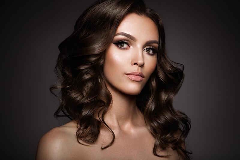 Kobieta o ciemnych, brązowych, kręconych włosach.
