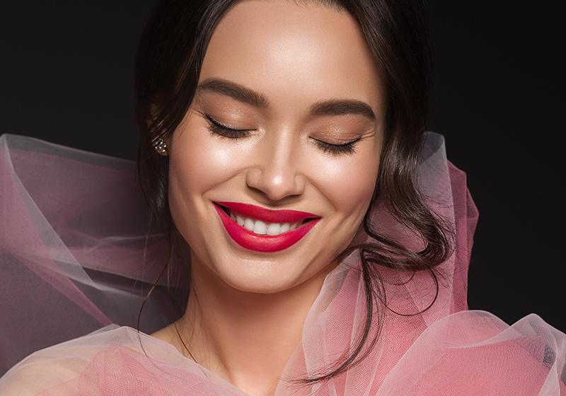 Uśmiechnięta kobieta z czerwoną szminką na ustach.