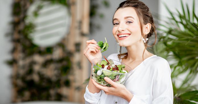 Dieta oczyszczająca: młoda kobieta je zdrową sałatkę.