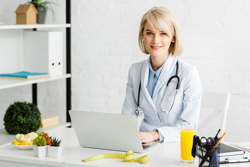 Uśmiechnięta kobieta dietetyk przy biurku z laptopem.