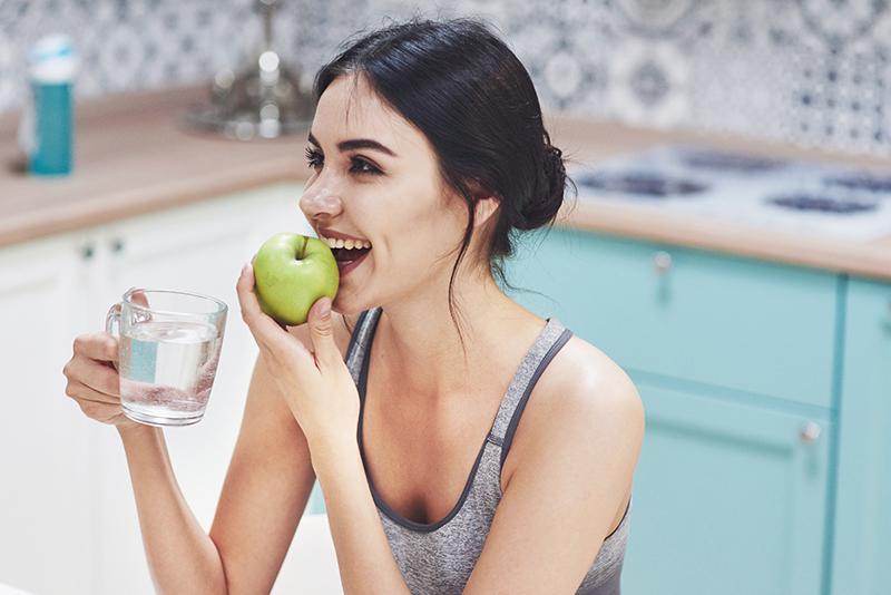 Dieta oczyszczająca: młoda kobieta je jabłko i pije wodę.