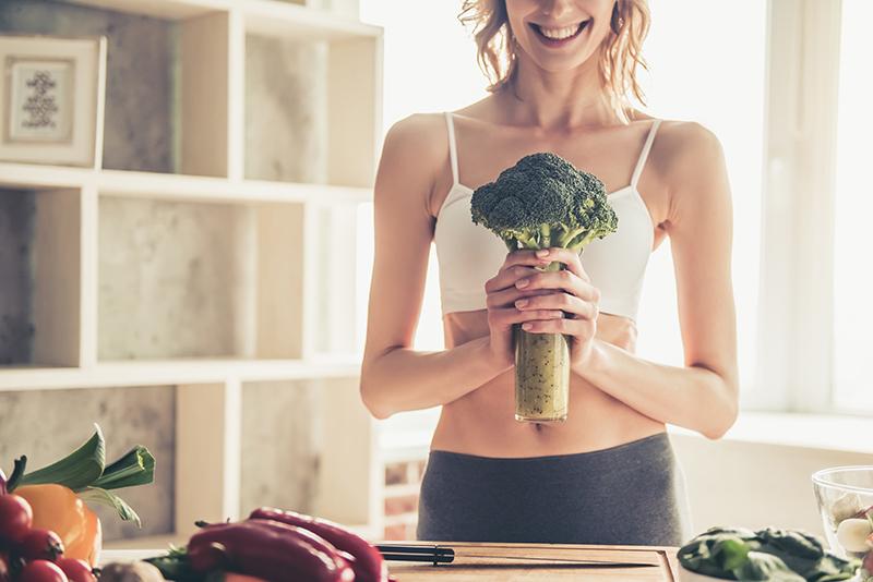Dieta oczyszczająca: uśmiechnięta kobieta w kuchni trzyma w rękach brokuły i wyciśnięty zielony sok w butelce.