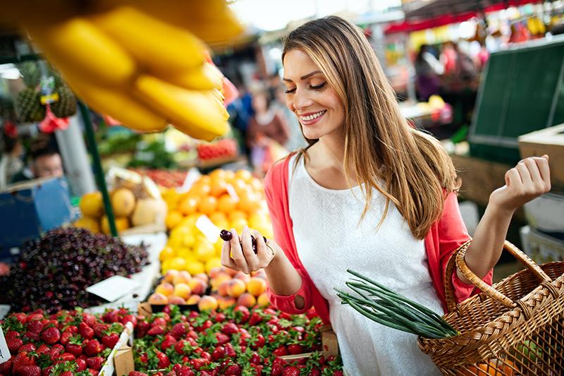 Młoda kobieta kupuje owoce na targu.