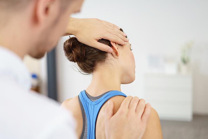 Fizjoterapeuta sprawdza czy kręgosłup jest zdrowy.