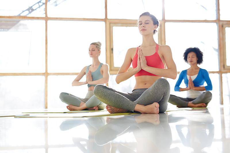 Trzy kobiety medytują na zajęciach jogi, poszukując wewnętrznej równowagi.