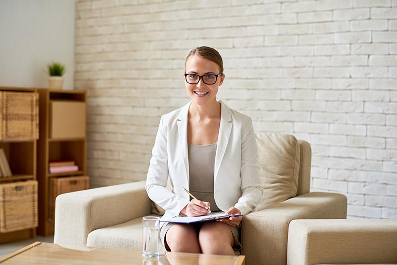 Portret pięknej młodej pani psycholog patrzącej na aparat z czarującym uśmiechem i robiącej notatki