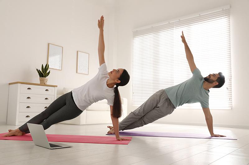 Para ćwiczy w domu, wykonując boczną deskę, zachowując zdrowy kręgosłup.