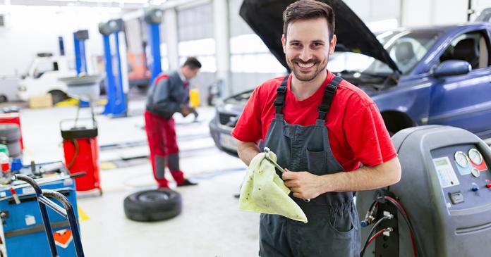 Uśmiechnięty mechanik w warsztacie samochodowym.