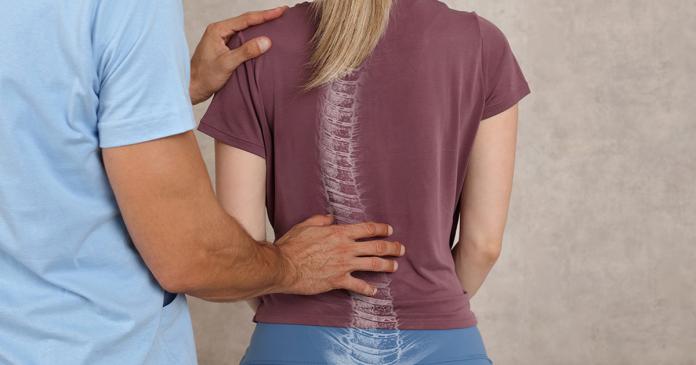 Fizjoterapeuta bada kręgosłup.