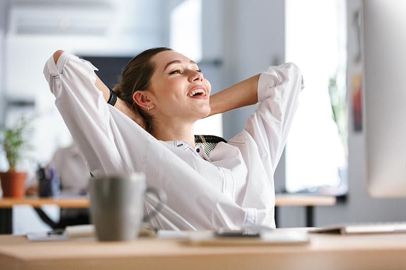 Uśmiechnięta kobieta z dłońmi splecionymi na karku odpoczywa przy biurku, dbając o zdrowy kręgosłup.