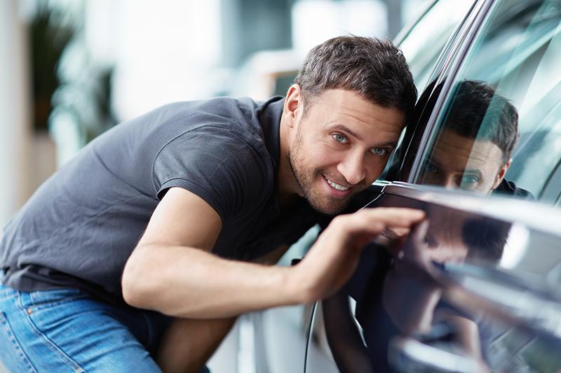 Młody mężczyzna z uśmiechem przygląda się karoserii samochodu.