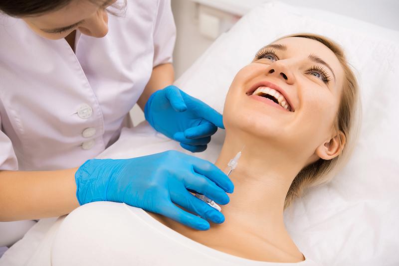 Uśmiechnięta kobieta podczas zabiegu z zakresu medycyny estetycznej.