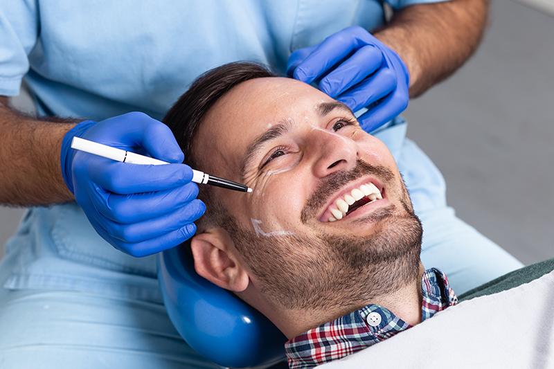 Lekarz medycyny estetycznej przygotowuje mężczyznę do zabiegu.