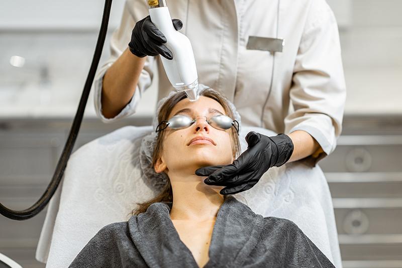 Kobieta w średnim wieku podczas zabiegu laserem na twarz.
