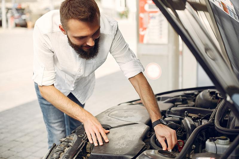 Mężczyzna sprawdza samochód przed kupnem