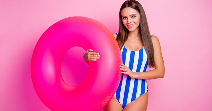 Kobieta w jednoczęściowym kostiumie kąpielowym z różowym kołem ratunkowym.