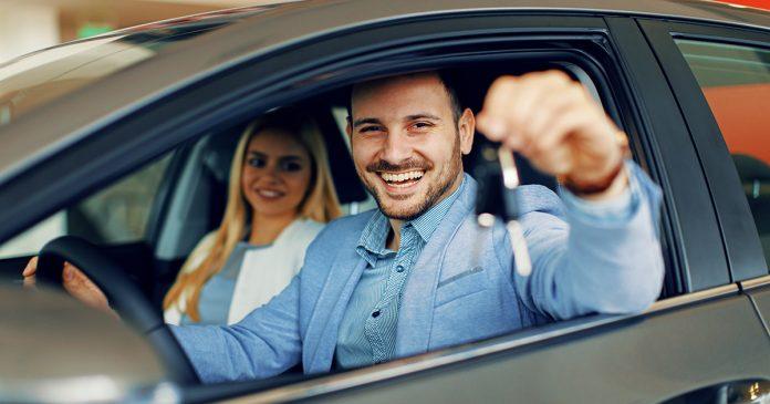 Para w samochodzie. Mężczyzna trzyma kluczyk w ręku.