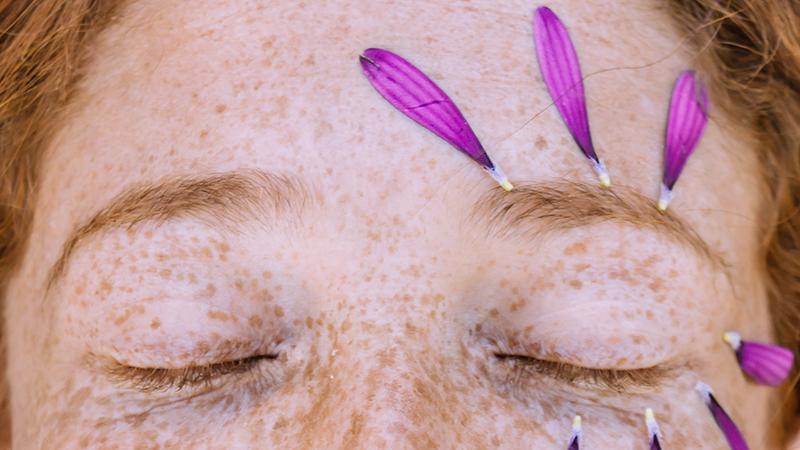 Zamknięte oczy kobiece z płatkami kwiatków wokół prawego oka.