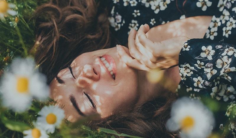 Kobieta leżąca na łące wśród rumianków.