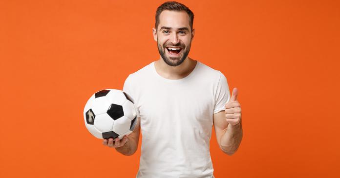 Fan piłki nożnej na pomarańczowym tle z piłką w ręku.