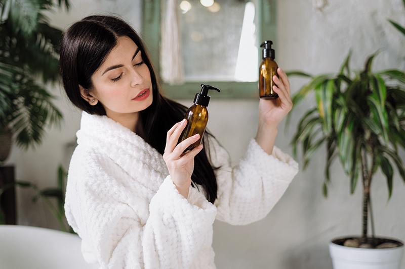 Kobieta w szlafroku, przyglądająca się opakowaniom kosmetyków. Pielęgnacja zero waste.