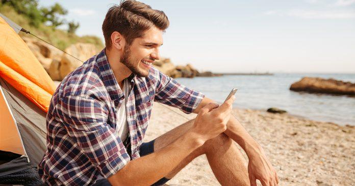 Mężczyzna na plaży z telefonem w ręku