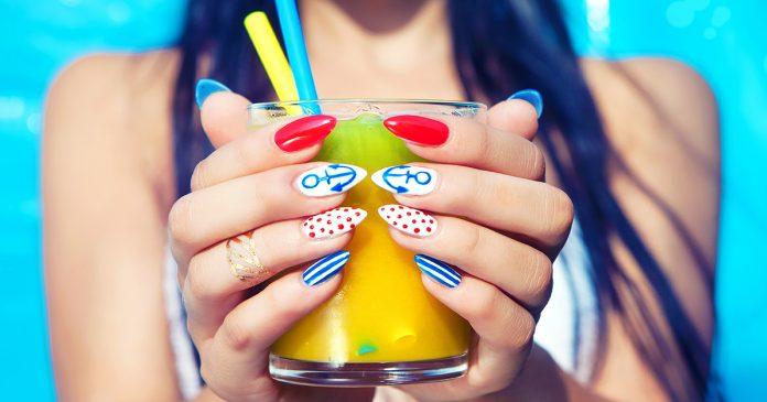 Wakacyjne paznokcie - młoda kobieta z marynarskim manicure trzymająca szklankę z sokiem pomarańczowym
