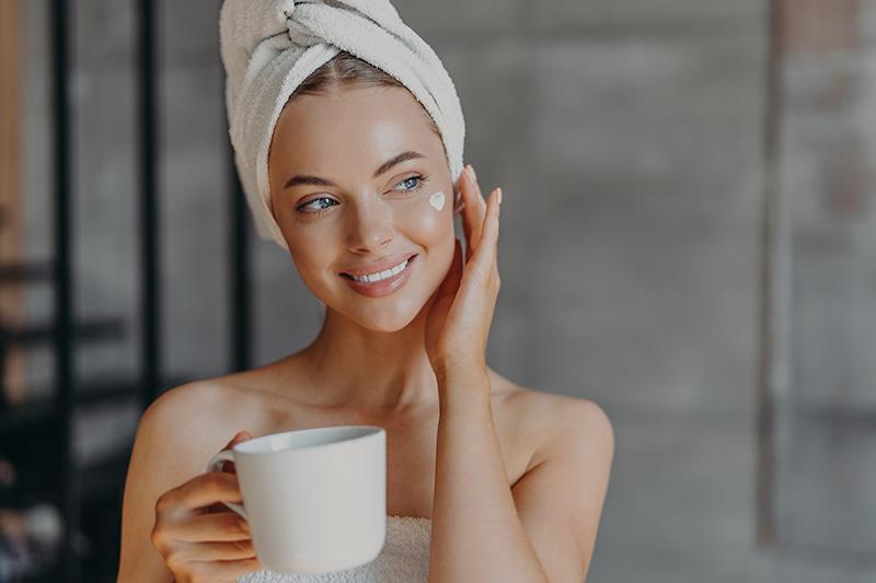 Piękna urocza młoda kobieta delikatnie dotyka twarzy, nakłada krem na twarz, ma minimalny makijaż, delikatnie się uśmiecha, na głowie ma zawinięty biały ręcznik kąpielowy, pije aromatyczną kawę, spędza wolny czas w domu