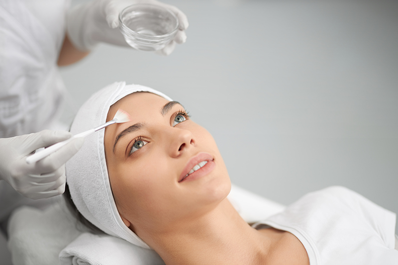 Kosmetyczka nakłada retinol na twarz młodej kobiety.