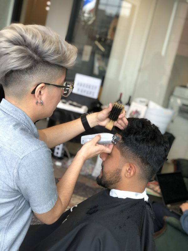 barber giving client a fade haircut with clippers and brush