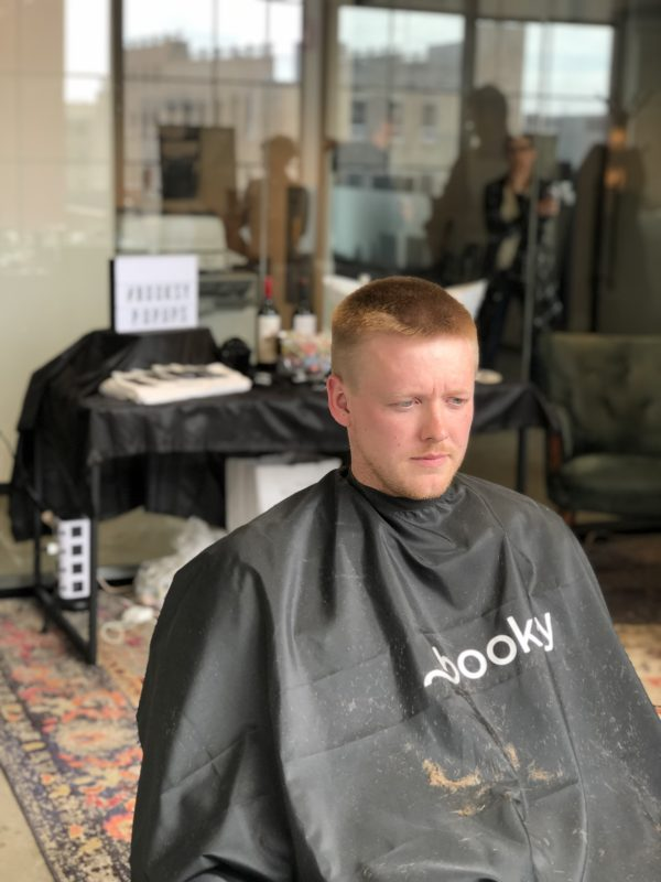 client wearing a booksy cape with a fresh haircut