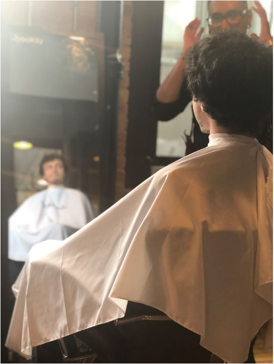 client looking into mirror with barber