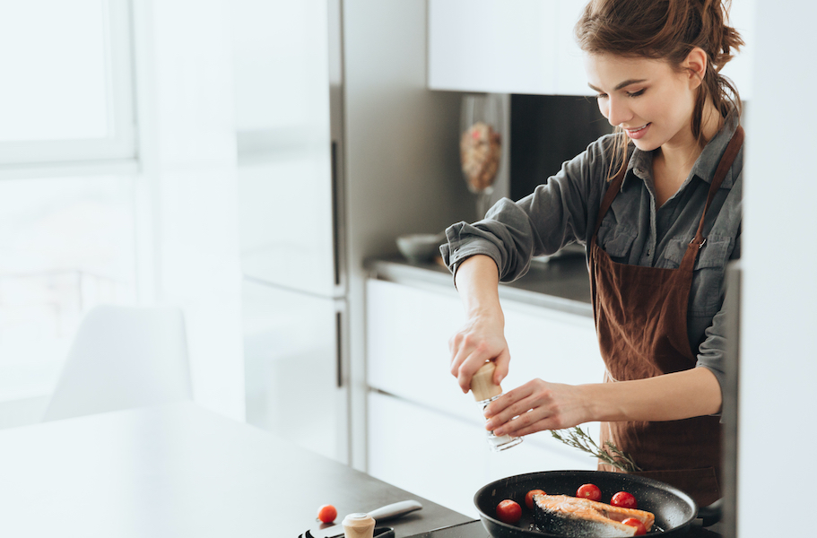 Woman de-stressing at home by cooking a nutritious meal.