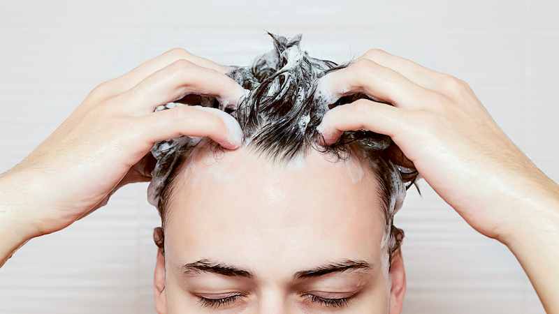 Man using conditioner to wash his hair.