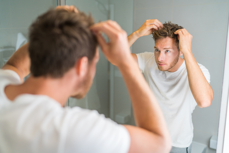 Man judging what to put into his hair.