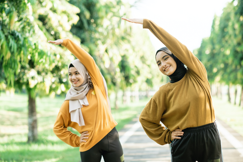 Two friends stretching before working out.