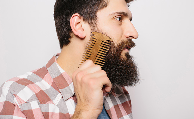 Man maintaining beard while working in beard oil