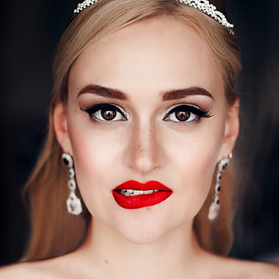 A bride posing with a red deep pout.
