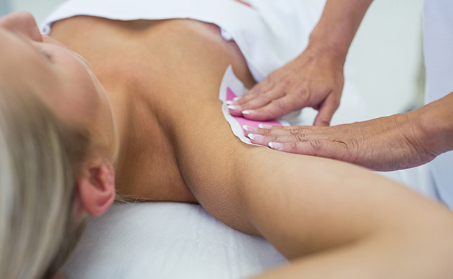 Woman getting her underarms waxed.