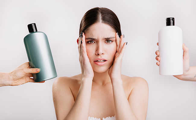 A woman confused about products for oily hair.