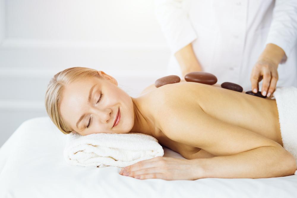 A woman getting a hot stone massage.