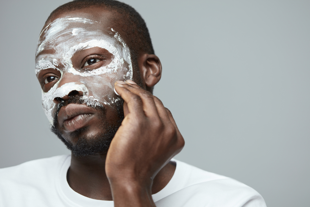 A man cleansing his skin.