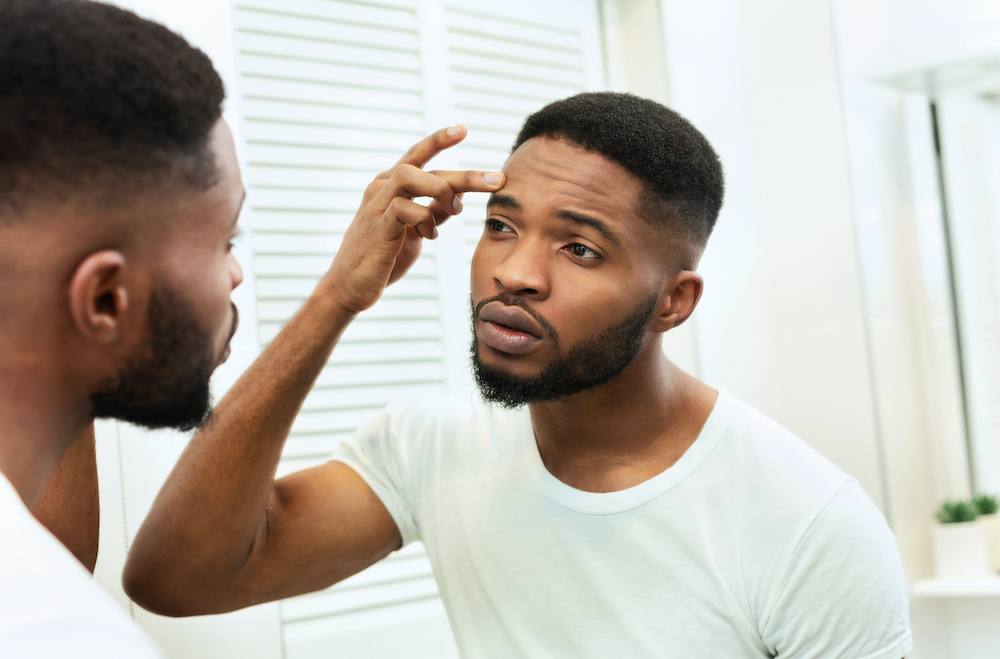A man inspecting his skincare.